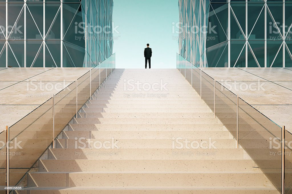 Businessman on the top of stairway between business centers outd stock photo
