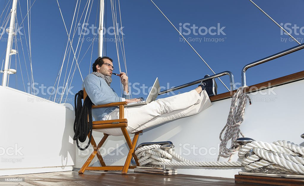 Businessman on the yacht smoking pipe and reading e-mails royalty-free stock photo