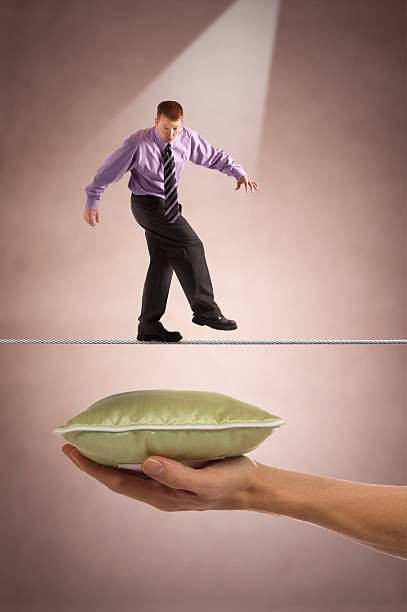 Businessman on tightrope with safety below stock photo