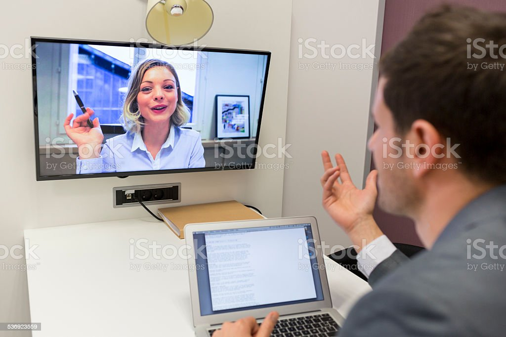Businessman on video conference with her colleague in office job stock photo