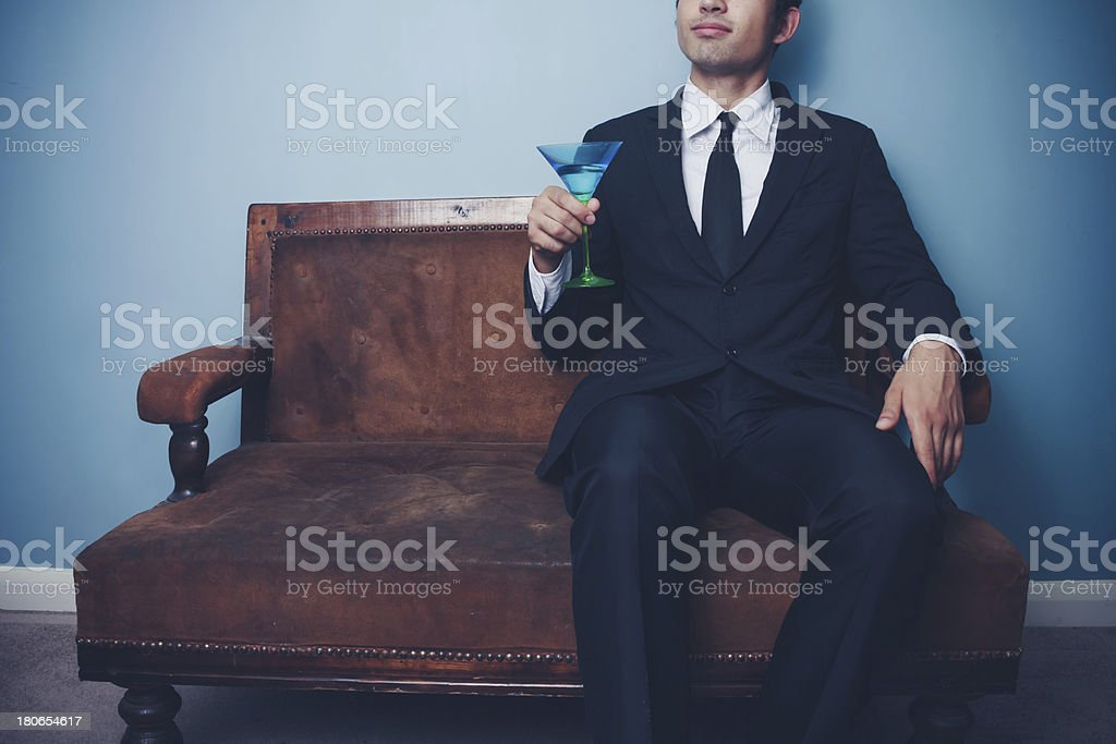 Businessman on vintage sofa drinking cocktail royalty-free stock photo