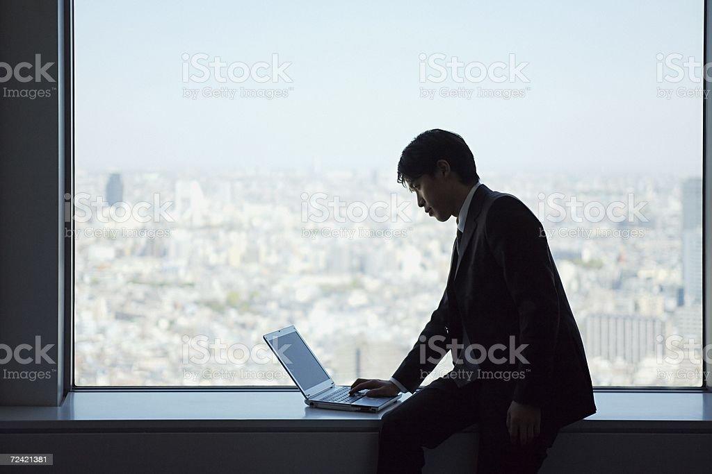 Businessman on window ledge with laptop royalty-free stock photo