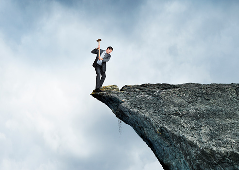 A businessman swings a sledge hammer against a rocky cliff as he stands on the wrong side placing himself at great risk.