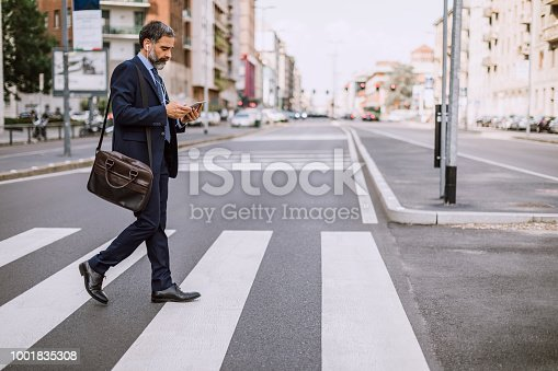 Mature Businessman Crossing The Street And Using Phone