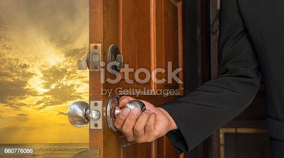 istock businessman open the door to sunset and sea scene 660776086