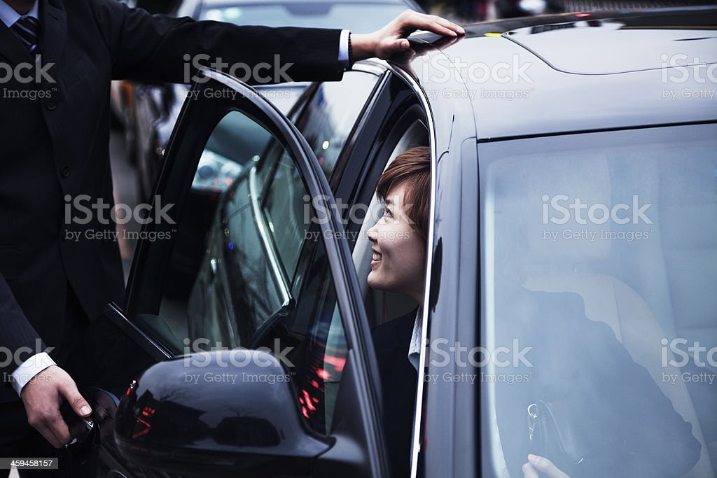 Businessman opening car door for businesswoman stock photo