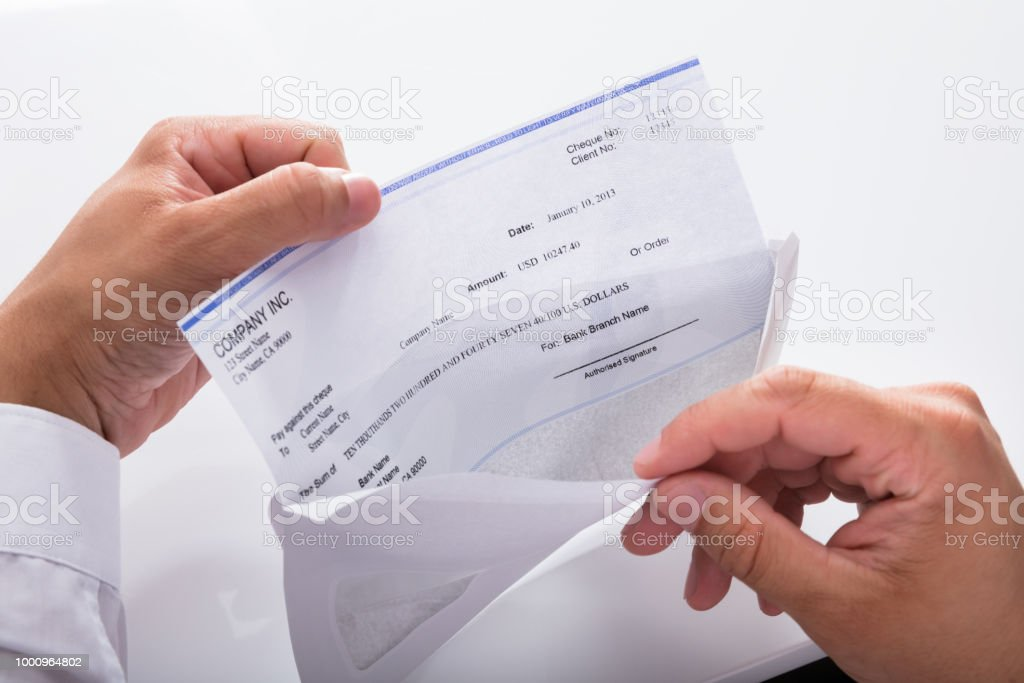 Businessman opening envelope with paycheck stock photo