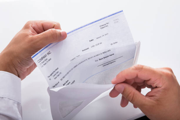 Businessman opening envelope with paycheck Close-up of a businessman's hand opening envelope with paycheck wages stock pictures, royalty-free photos & images