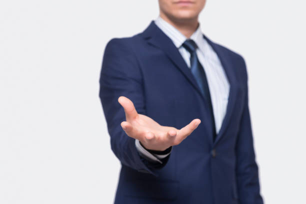 businessman opening hand over gray background | background for hologram - palmo foto e immagini stock