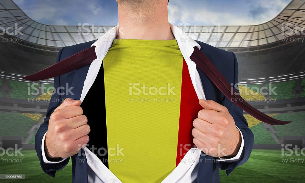 Businessman opening shirt to reveal belgium flag stock photo