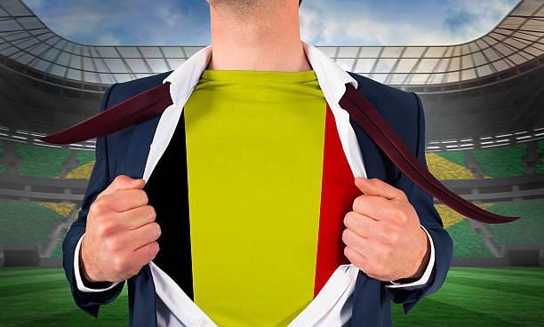 Businessman opening shirt to reveal belgium flag stock photo