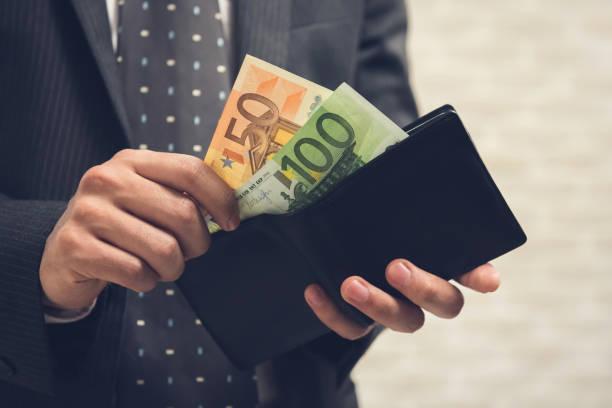 m-cüzdan açılması ve bazı para, euro para alarak iş adamı - bearn stok fotoğraflar ve resimler