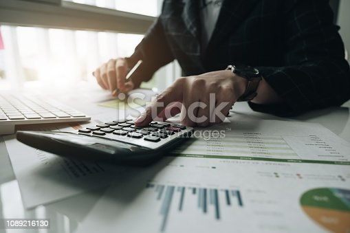 897852992istockphoto businessman or accountant hand holding pen working on calculator to calculate business data, accountancy document and laptop computer at office, business concept 1089216130