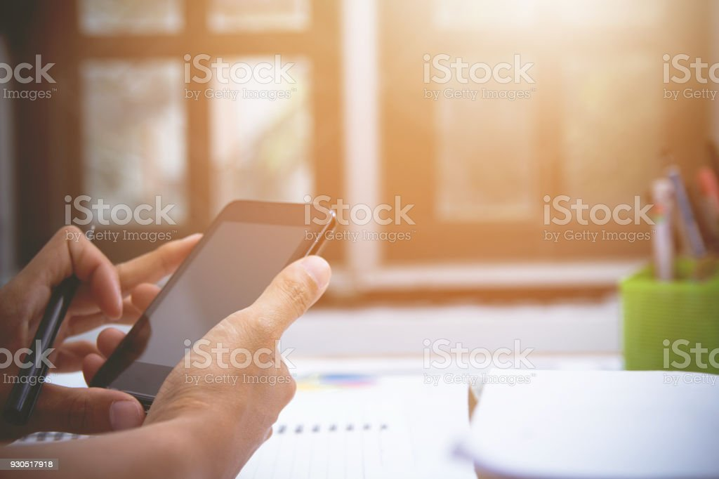 Businessman or accountant, pen holder, mobile accounting and calculator,working on the table with sunset light. stock photo