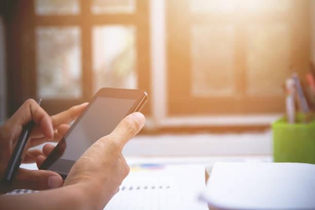 実業家または会計士、ペンホルダー、モバイル会計、計算機、夕日の光でテーブルを扱っています。 - パラリーガル ストックフォトと画像