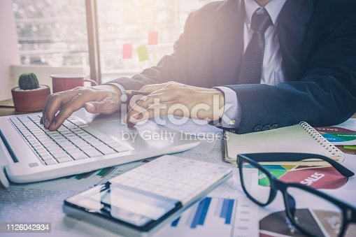istock Businessman or accountant working on calculator to calculate business data concept. Accounting,investment advisor consulting situation on the financial report and planning a marketing plan at office. 1126042934