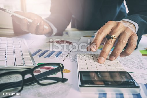 istock Businessman or accountant working on calculator to calculate business data concept. Accounting,investment advisor consulting situation on the financial report and planning a marketing plan at office. 1126042948