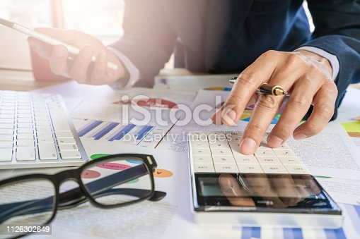 952991586istockphoto Businessman or accountant working on calculator to calculate business data concept. Accounting,investment advisor consulting situation on the financial report and planning a marketing plan at office. 1126302649
