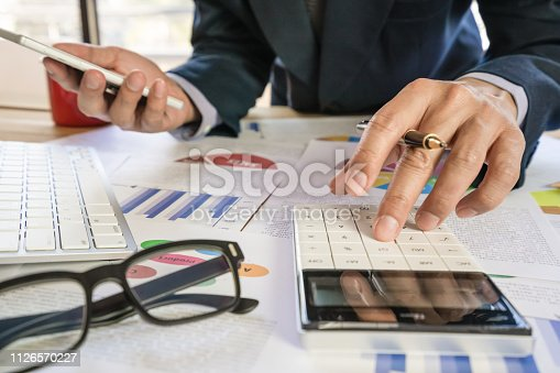 istock Businessman or accountant working on calculator to calculate business data concept. Accounting,investment advisor consulting situation on the financial report and planning a marketing plan at office. 1126570227