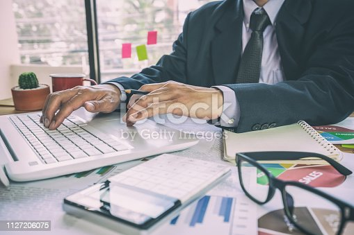 istock Businessman or accountant working on calculator to calculate business data concept. Accounting,investment advisor consulting situation on the financial report and planning a marketing plan at office. 1127206075