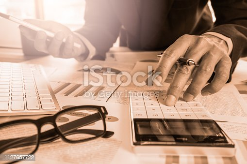 952991586istockphoto Businessman or accountant working on calculator to calculate business data concept. Accounting,investment advisor consulting situation on the financial report and planning a marketing plan at office. 1127657722