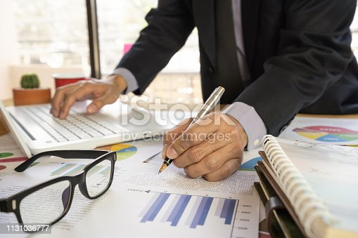 istock Businessman or accountant working on calculator to calculate business data concept. Accounting,investment advisor consulting situation on the financial report and planning a marketing plan at office. 1131036777