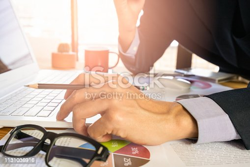 istock Businessman or accountant working on calculator to calculate business data concept. Accounting,investment advisor consulting situation on the financial report and planning a marketing plan at office. 1131036916