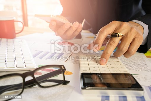 istock Businessman or accountant working on calculator to calculate business data concept. Accounting,investment advisor consulting situation on the financial report and planning a marketing plan at office. 1131266358