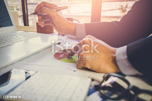 istock Businessman or accountant working on calculator to calculate business data concept. Accounting,investment advisor consulting situation on the financial report and planning a marketing plan at office. 1131909478