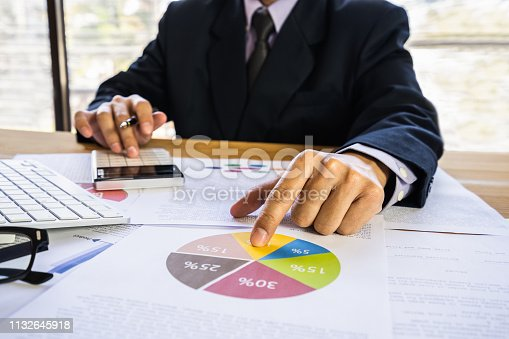 952991586istockphoto Businessman or accountant working on calculator to calculate business data concept. Accounting,investment advisor consulting situation on the financial report and planning a marketing plan at office. 1132645918