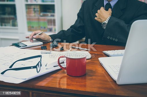952991586istockphoto Businessman or accountant working on calculator to calculate business data concept. Accounting,investment advisor consulting situation on the financial report and planning a marketing plan at office. 1182549225