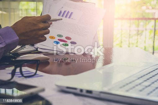 952991586istockphoto Businessman or accountant working on calculator to calculate business data concept. Accounting,investment advisor consulting situation on the financial report and planning a marketing plan at office. 1183849935