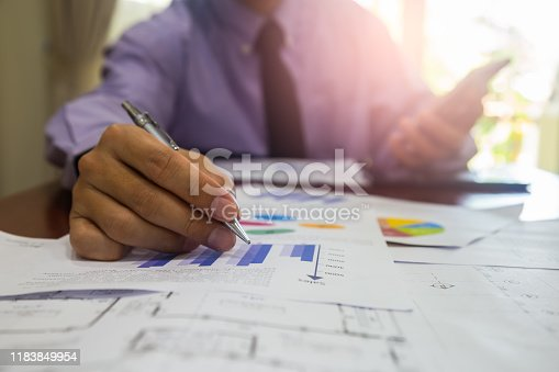 952991586istockphoto Businessman or accountant working on calculator to calculate business data concept. Accounting,investment advisor consulting situation on the financial report and planning a marketing plan at office. 1183849954