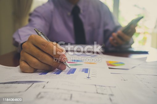 952991586istockphoto Businessman or accountant working on calculator to calculate business data concept. Accounting,investment advisor consulting situation on the financial report and planning a marketing plan at office. 1184064820