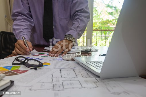 952991586istockphoto Businessman or accountant working on calculator to calculate business data concept. Accounting,investment advisor consulting situation on the financial report and planning a marketing plan at office. 1184730202
