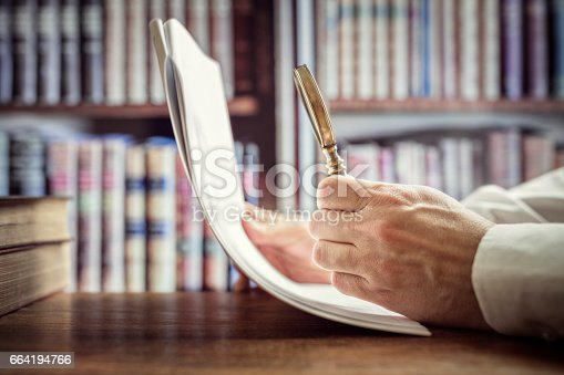 istock Businessman or attorney with magnifying glass reading documents 664194766