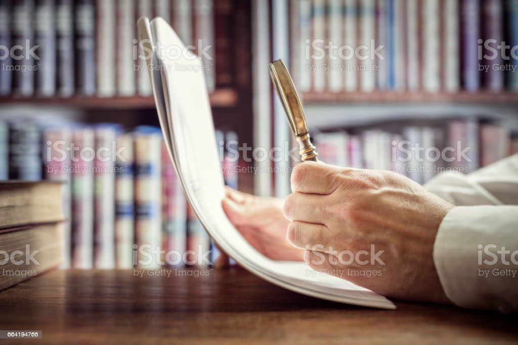 Businessman or attorney with magnifying glass reading documents stock photo