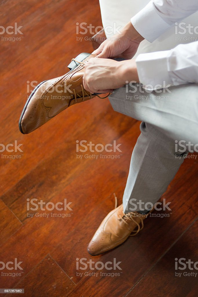 Businessman or groom wearing his brown shoes Lizenzfreies stock-foto