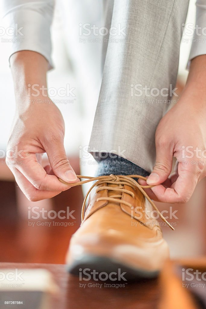 Businessman or groom wearing his brown shoes royalty-free stock photo