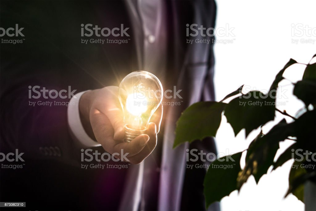 Businessman or man in a suit holding an illuminated light bulb in hand. - Foto stock royalty-free di Adulto