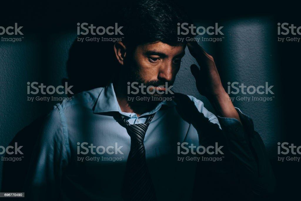 Businessman or political prisoner in dark cell. Concept of white collar crime stock photo
