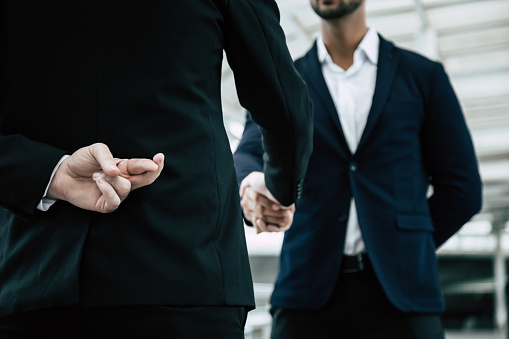 istock Businessman or politician cross finger, hiding behind his back during he get handshake to another person, businessman. Businessman pretend to be good person, he is liar. White collar worker is fraud 1185903411
