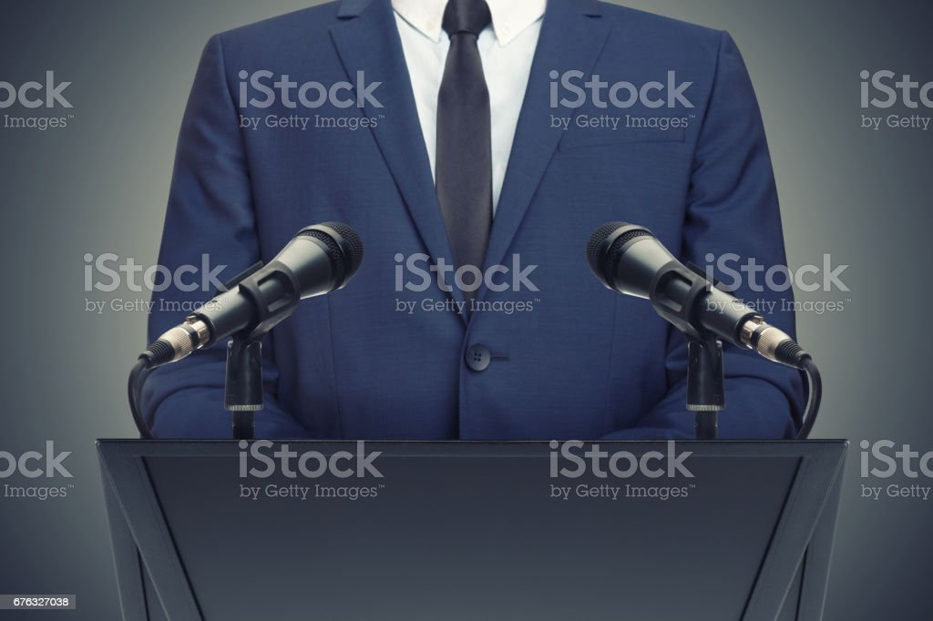 Businessman or politician making speech behind the pulpit - foto de acervo