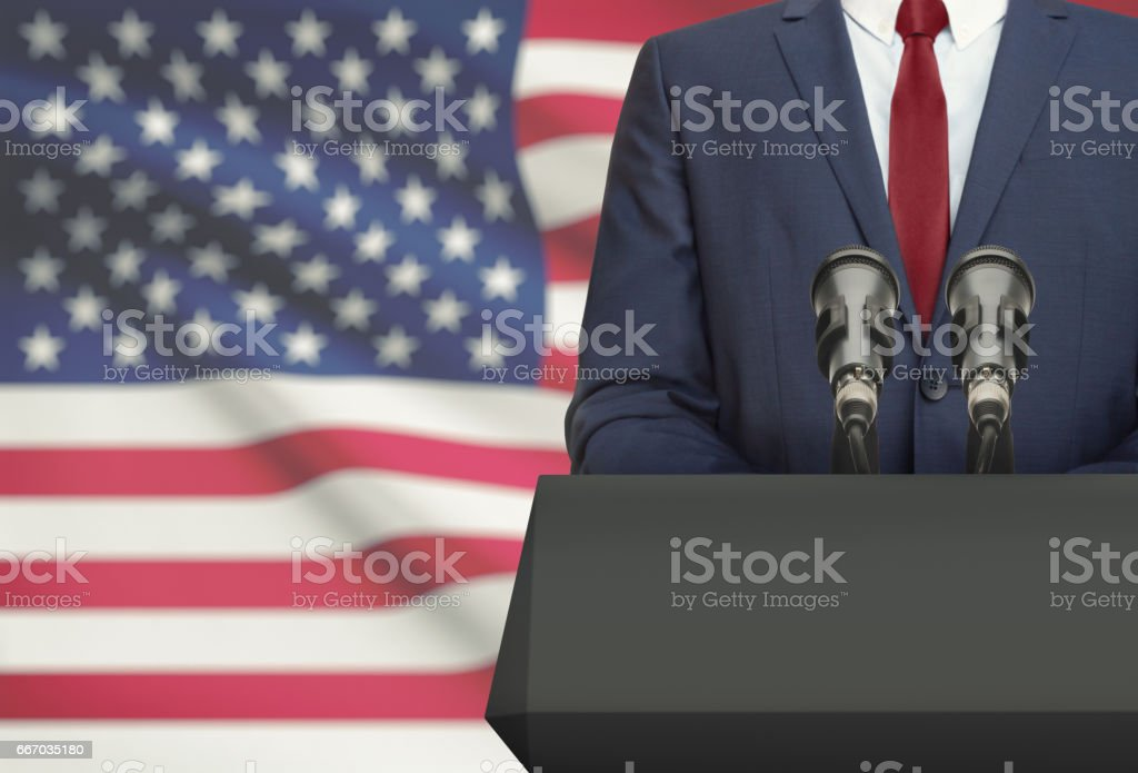 Businessman or politician making speech from behind a pulpit with national flag on background - United States stock photo