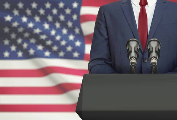 businessman or politician making speech from behind a pulpit with national flag on background - united states - politician stock photos and pictures
