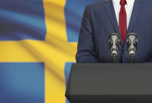 businessman or politician making speech from behind a pulpit with national flag on background - sweden - politique et gouvernement photos et images de collection