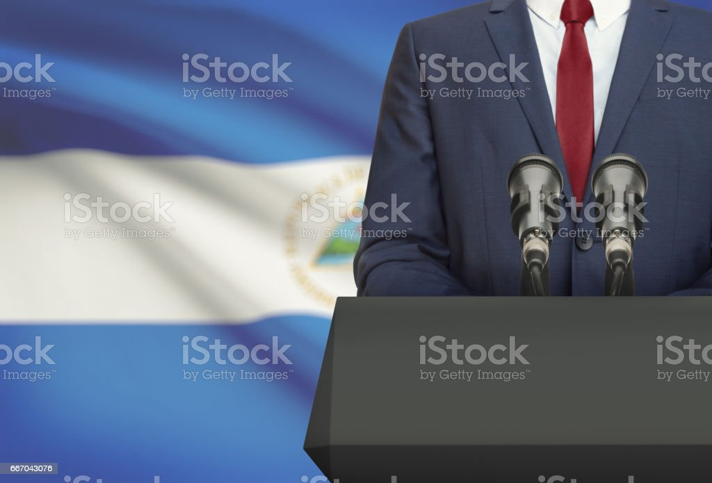 Businessman or politician making speech from behind a pulpit with national flag on background - Nicaragua - foto de stock