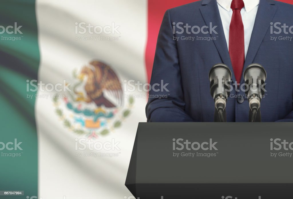 Businessman or politician making speech from behind a pulpit with national flag on background - Mexico stock photo