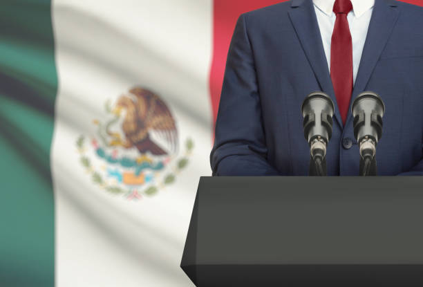 businessman or politician making speech from behind a pulpit with national flag on background - mexico - президент стоковые фото и изображения