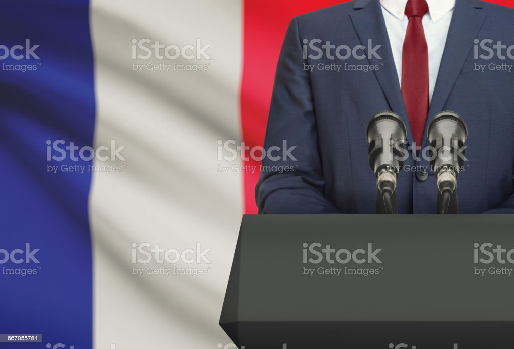 Businessman or politician making speech from behind a pulpit with national flag on background - France stock photo
